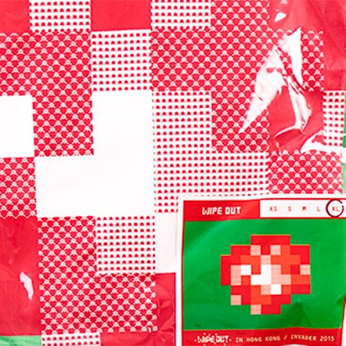 close up detail of invader wipe out green and red t-shirt showing invader detail and size