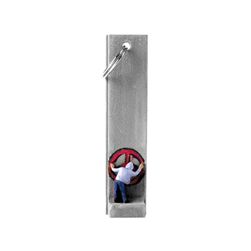 banksy walled off hotel key fob key chain with man in hoodie painting a red peace sign on section of wall