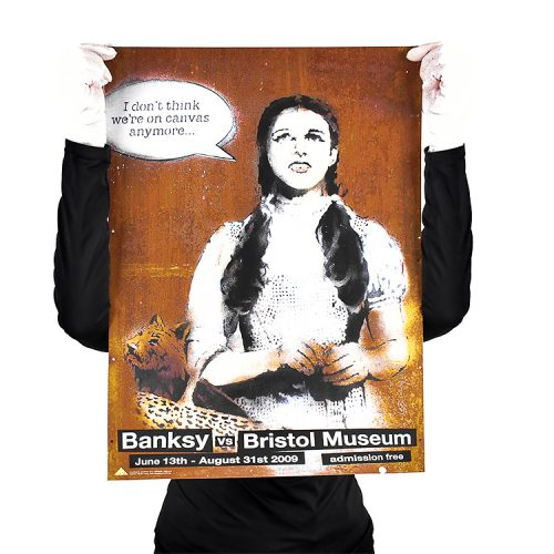 person holding banksy dorothy poster from banksy vs bristol museum show for scale