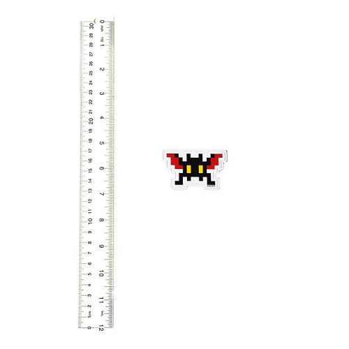 invader sticker black with red wings next to ruler for scale