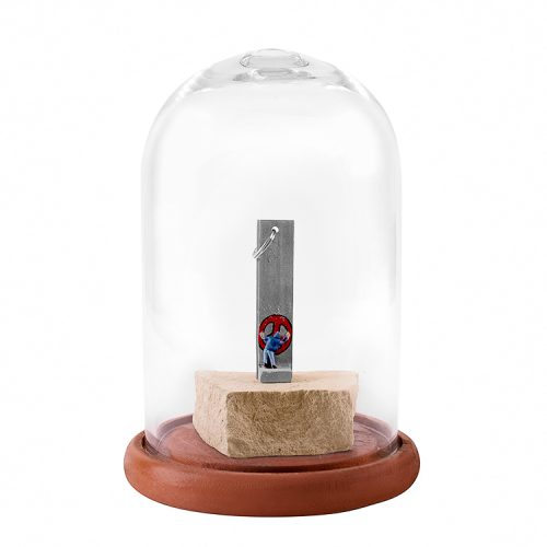 banksy walled off hotel sculpture of graffiti artist painting red peace sign in clear dome display case