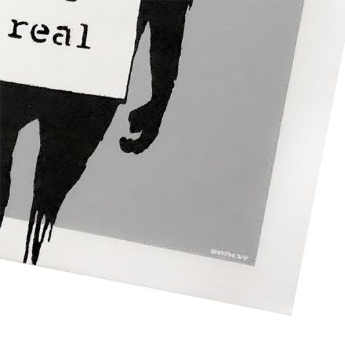 banksy keep it real laugh now silver close up of banksy signature on keep it real side of cover